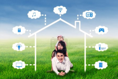 Photo for Asian family smiling at the camera while lying on the meadow under smart house network design - Royalty Free Image