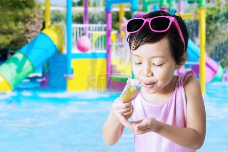 Little child eating ice cream at pool