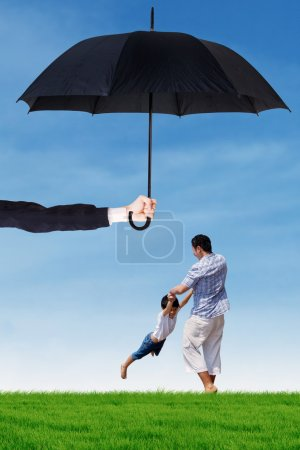 Dad and his boy playing under umbrella at field