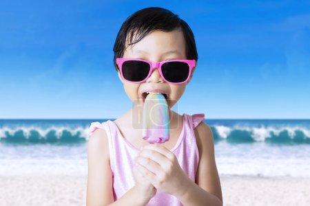 Female child eats ice cream at shore