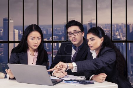 Multi ethnic employees discussing in office