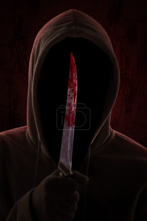 A dangerous hooded man standing in the dark and ho...