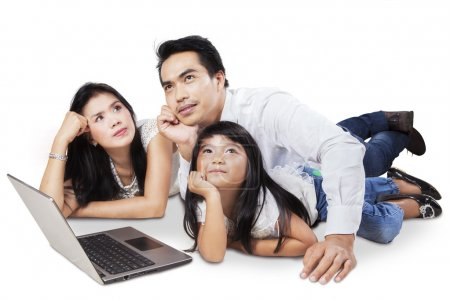 Photo pour Three member of happy family with laptop computer and dreaming something - image libre de droit