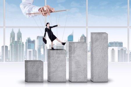 Photo pour Femme entrepreneur attaché sur les cordes et marcher sur le graphique d'affaires avec contrôlée par quelqu'un - image libre de droit