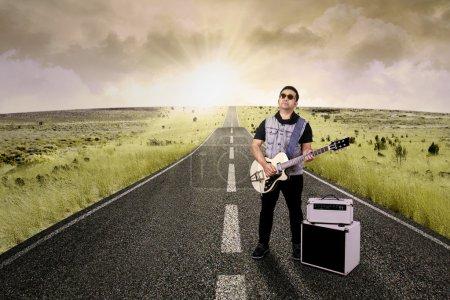 Hispanic guitarist plays guitar on the street
