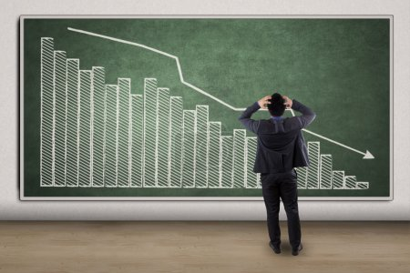 Photo for Side view of disappointed businessman looking at chart showing economic recession - Royalty Free Image