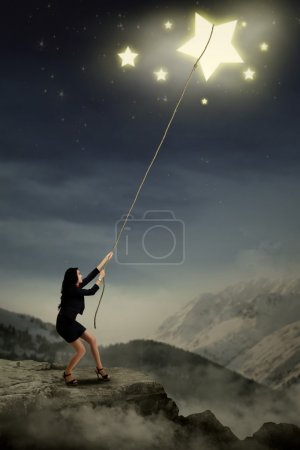 Photo for Portrait of young businesswoman taking stars from the sky space - Royalty Free Image