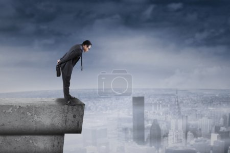 Businessman standing on rooftop and look down