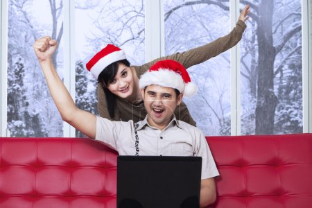 Happy couple on sofa with laptop in xmas day