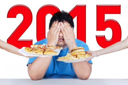 Photo pour Overweight person closing his face from junk food, symbolizing he planning to healthy life in 2015 - image libre de droit