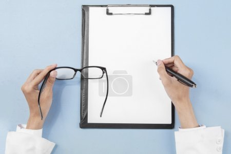 Doctor hands with glasses writing on paper