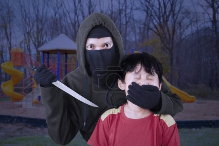 Photo for Scared child with an adult man's hand covering her mouth and threatening using a knife - Royalty Free Image