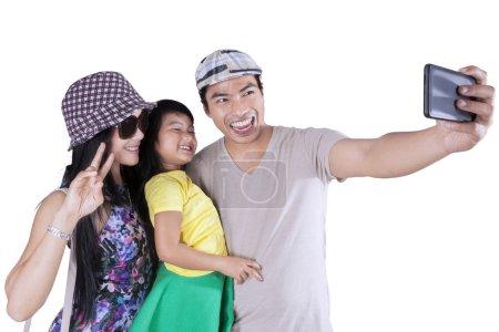 Joyful family taking pictures in studio