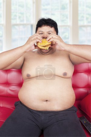 Obesity person eating burger on sofa
