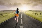 Female runner running at road
