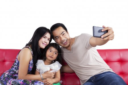 Family taking self picture on sofa