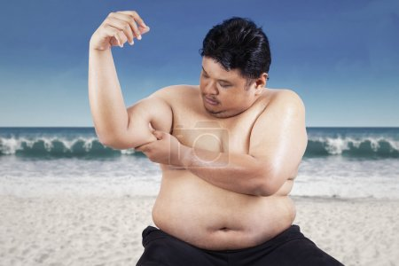 Fat man holding his flabby biceps