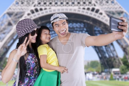 Family taking photo with camera phone in Paris