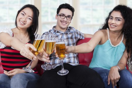 Multiracial teenagers toast with beer