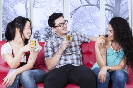 Multiracial teenager drinking beer on sofa