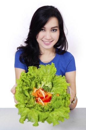 Pretty asian woman showing salad