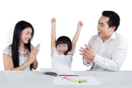Photo pour Petite fille joyeuse lèvent la main après avoir terminé son affectation d'écoles et obtenir des applaudissements - image libre de droit