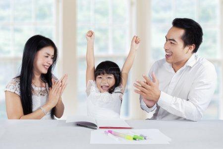 Photo pour Petite fille heureuse finissant ses devoirs et obtiennent des applaudissements de ses parents à la maison - image libre de droit