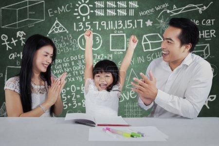 Photo pour La petite fille gaie obtiennent l'appréciation et les applaudissements de ses parents après étude - image libre de droit