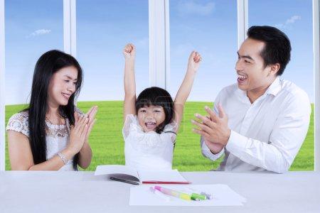 Photo pour Parents heureux applaudissant des mains pour apprécier leur fille après avoir fini des devoirs - image libre de droit