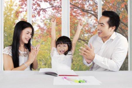 Photo pour Deux parents donnant des applaudissements à leur fille après avoir fini ses devoirs - image libre de droit