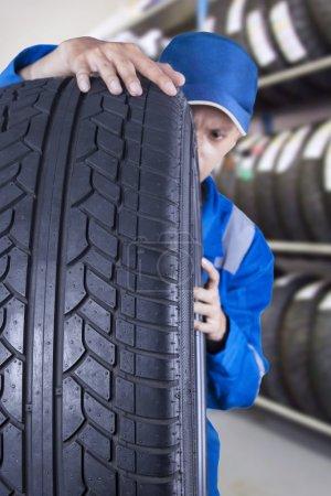 Male mechanic checks a tire seriously