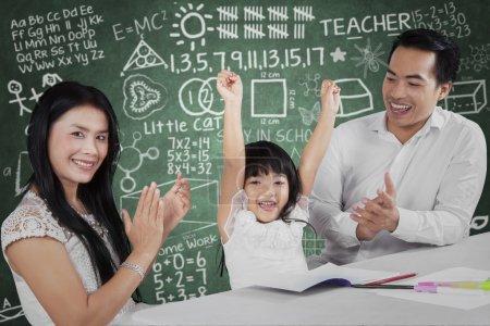 Photo pour Verticale de petite fille heureuse lèvent des mains après avoir fini ses devoirs et obtiennent des applaudissements - image libre de droit