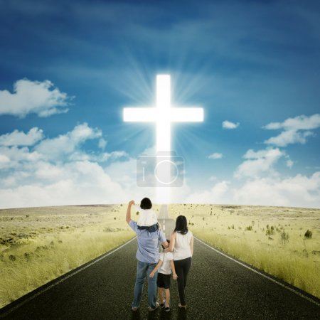 Photo for Back view of two parents standing on the road with their children looking at a cross - Royalty Free Image