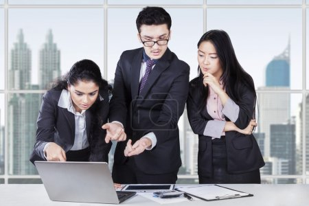 Business team discussing with laptop