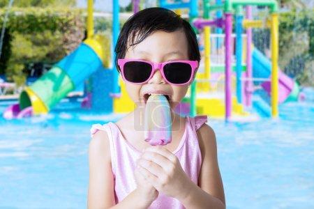 Sweet girl bite ice cream at pool
