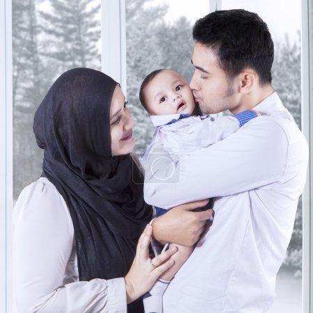 Photo pour Portrait de parents heureux embrassant leur petit bébé à la maison, tourné avec fond d'hiver sur la fenêtre - image libre de droit