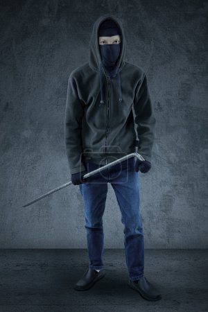 Male burglar ready to steal and carry a crowbar, w...