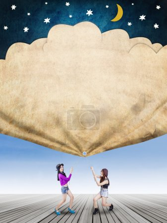 Girls pull a banner with stars and moon