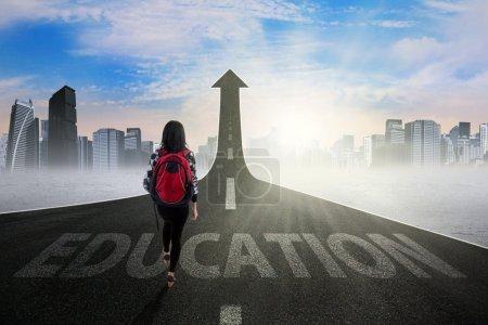 Photo pour Jeune étudiant marchant sur la route avec un texte de l'éducation se transformant en flèche vers le haut, symbolisant la façon d'accéder à l'enseignement supérieur - image libre de droit