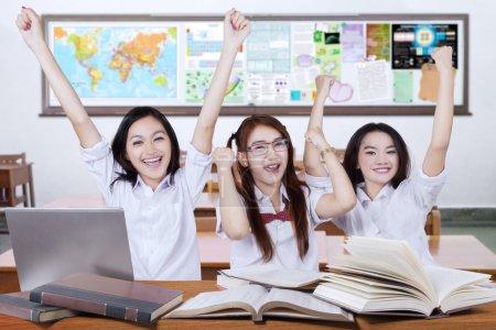 Three excited schoolgirls raise hands in the class