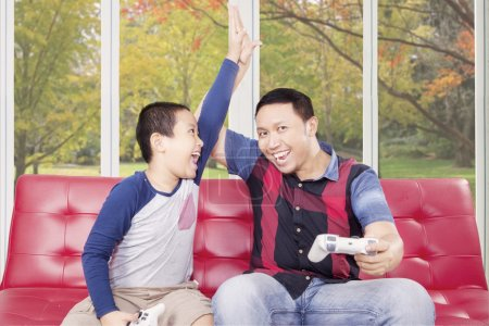 Cheerful dad playing video game with his son