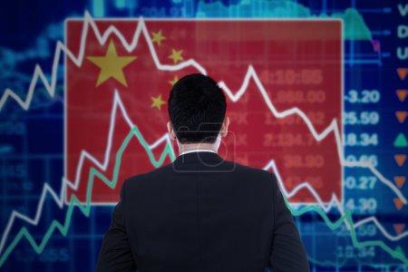 Photo pour Jeune homme d'affaires regardant un graphique boursier avec une flèche en déclin et le drapeau chinois - image libre de droit