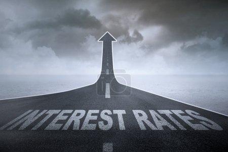 Photo pour Notion de taux d'intérêt plus élevée : les taux d'intérêt de mots sur une route droite, transformant en croissant de flèche - image libre de droit