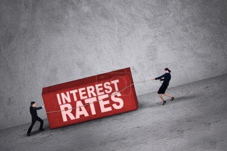 Photo pour Gens d'affaires essayant d'obtenir un bloc avec des taux d'intérêt mot là-dessus - image libre de droit