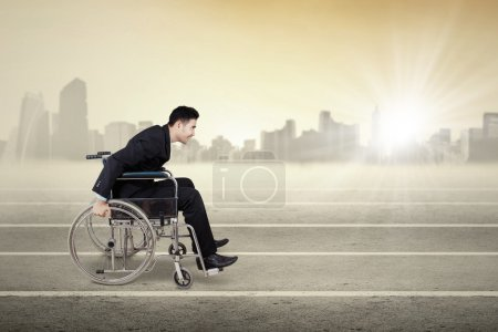 Disabled businessman pushing wheelchair outdoors