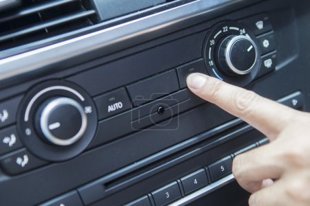 Finger pushing the air conditioner button