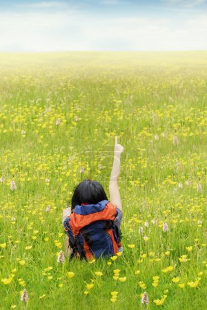 Female backpacker sitting on the meadow while carr...