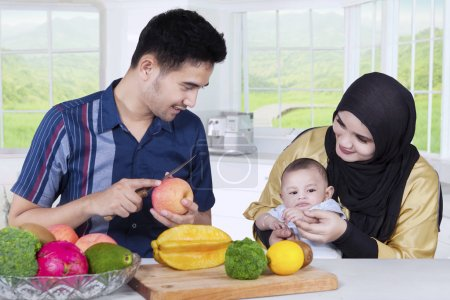 Photo for Portrait of happy asian family with their baby cooking together in the kitchen - Royalty Free Image