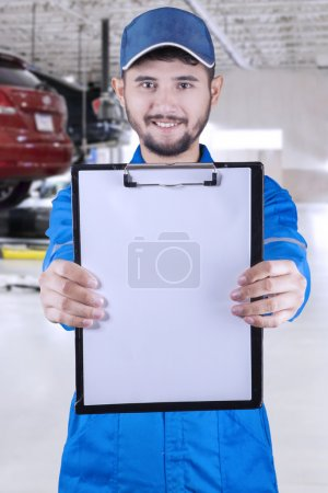Middle eastern mechanic holds copyspace