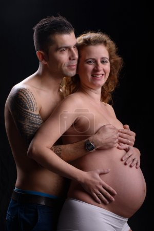 Photo for Happy couple pregnant woman studio portrait looking happy - Royalty Free Image